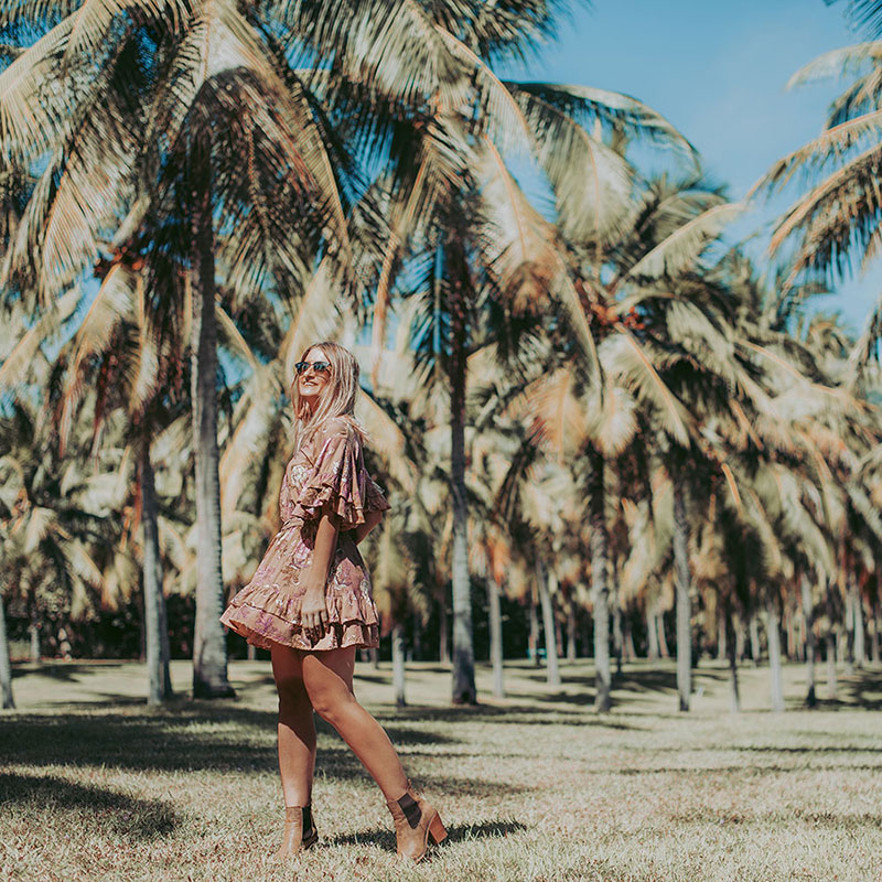 spell designs rosa playdress worn with tanned boots in field of palm trees fashion and travel instagram shot the daily luxe