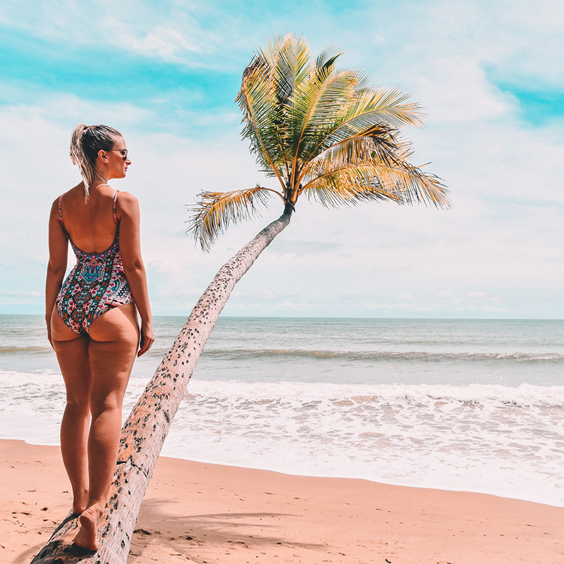 cairns fashion blogger the daily luxe wears Camilla Queen Kalbelia one piece swimsuit and climbs palm tree on tropical beach