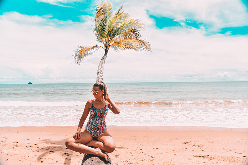 instagram fashion and travel blogger sits on palm tree on tropical australian beach at clifton beach near cairns wearing camilla one piece swimsuit