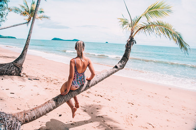fashion and travel instagrammer the daily luxe sits on palm tree on tropical cairns beach wearing one piece swimsuit.